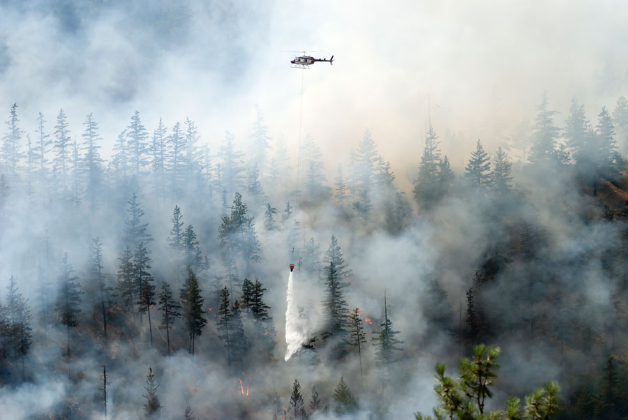 Helicopter in a smokey sky over forest fire