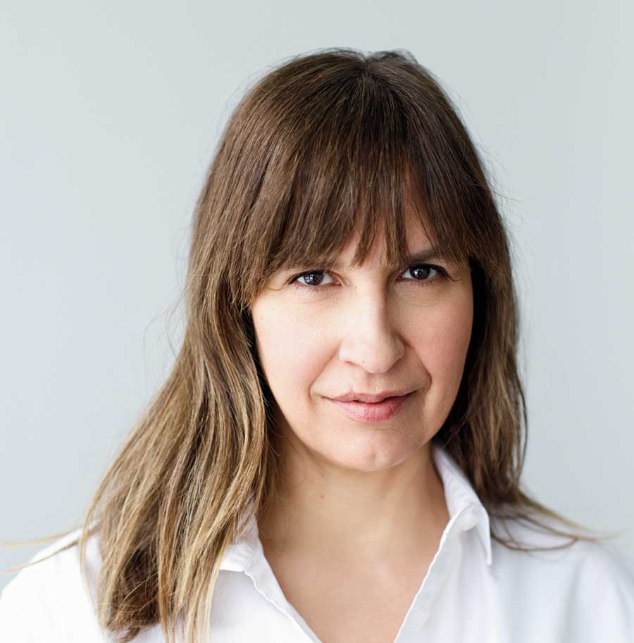 A portrait of Canadian Author Lisa Gabriele, bangs partially over her eyebrows, wearing a white dress shirt with the top button undone.