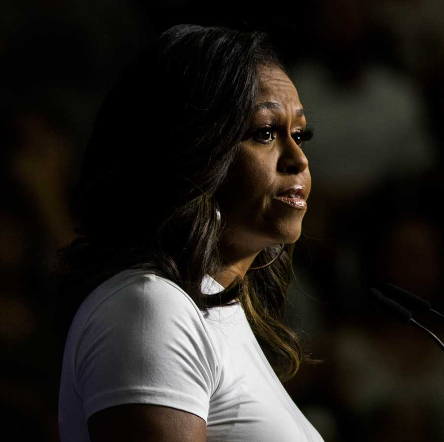 Michelle Obama shrouded in darkness gazing off camera.
