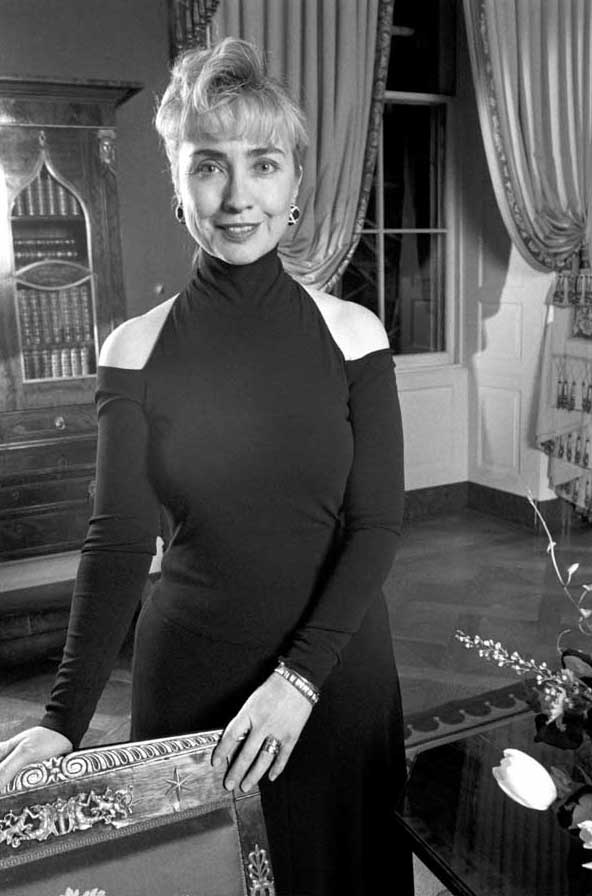 Hillary Clinton in a black off-the-shoulder dress sitting on a desk smiling.