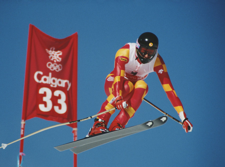 A skier in mid-air beside a promotional sign for the Calgary Olympics.