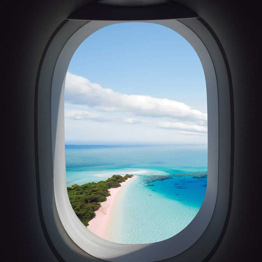 The view of a Caribbean Island seen through the window of an airplane.