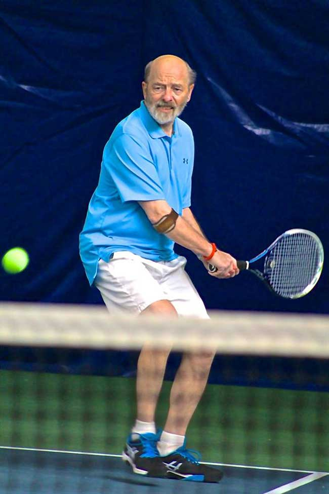 Older balding man prepares to take a swing at a tennis ball with his tennis racket.