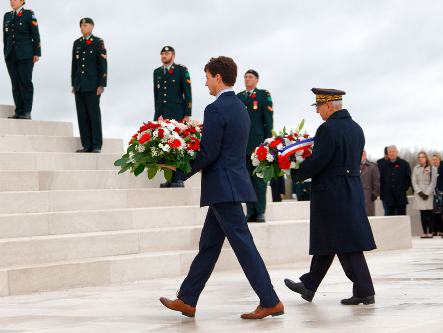 Trudeau and war veteran ascend the stairs of the Vimy Ridge Memorial to lay flowers at the centennial armistice celebration.