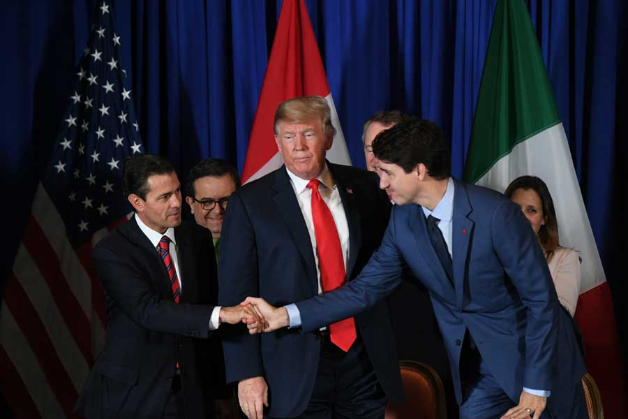 Trudeau and Mexican President shake hands as Trump looks unimpressed between them.