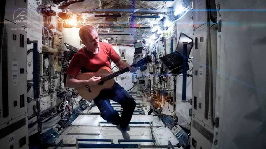 Chris Hadfield strums a guitar while floating aboard the international space station.