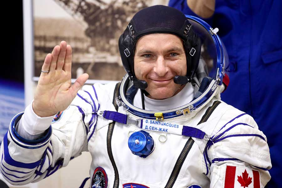 David Saint-Jacques waves in his space suit before launch to international space station.