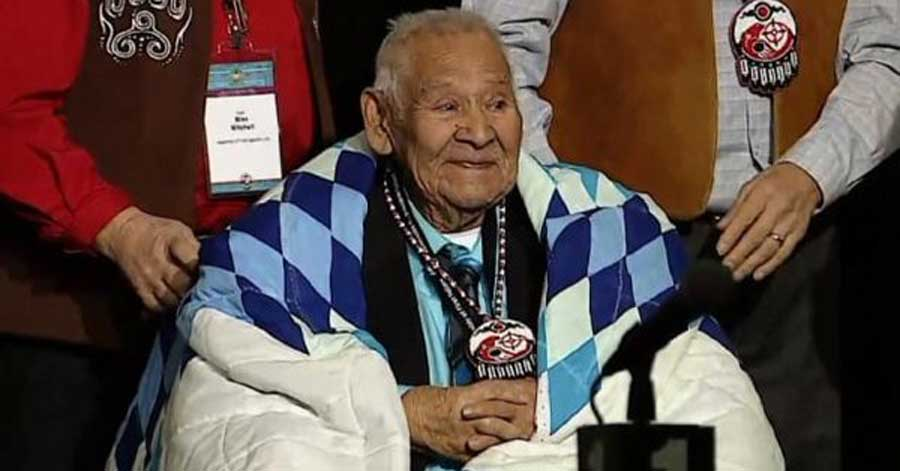 Louis Levi Oakes, the last surviving mohawk code talker from first world war, at a ceremony wrapped in a star blanket and wearing a beaded medallion.