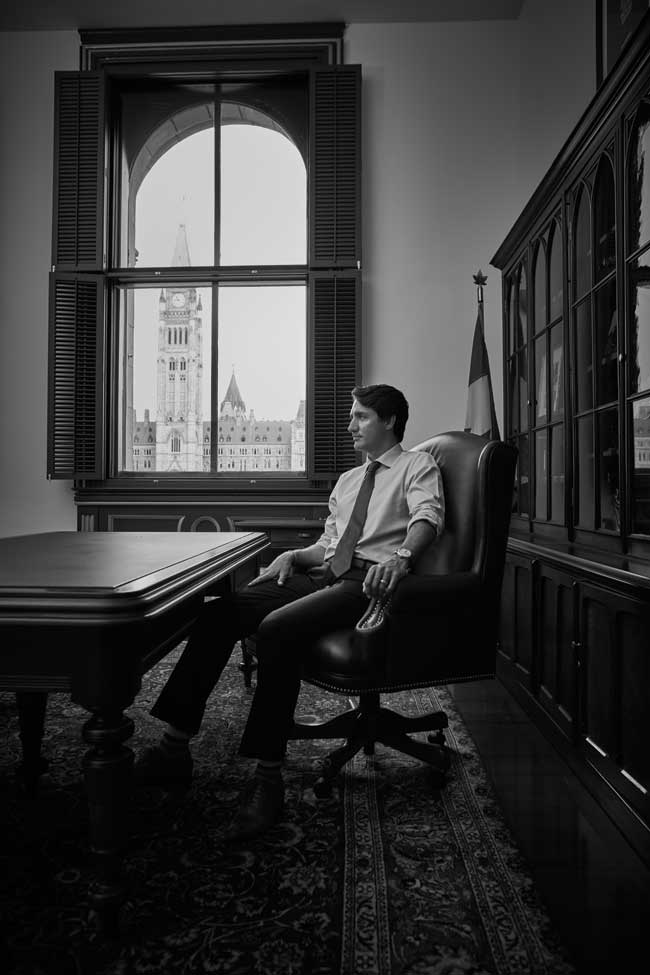 A black and white photo of Justin Trudeau sitting in his office in Ottawa.