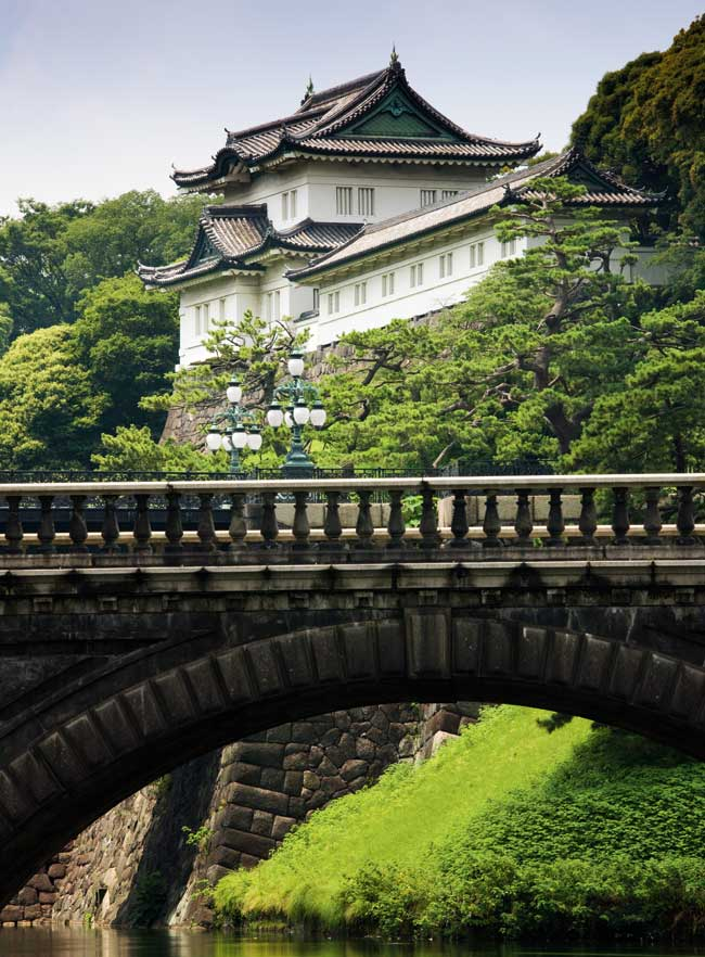 The entrance bridge to the Imperial Palace in Tokyo, surrounded by lush green trees.