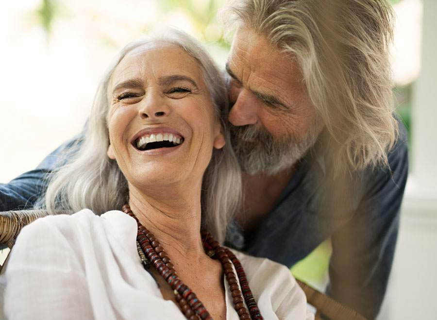 An older grey haired woman laughing as a man with long grey hair and a beard moves in to kiss her cheek.