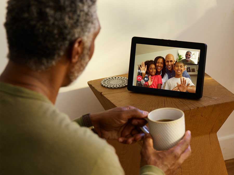 A man looking at a tablet-like screen with several of his family members on it.