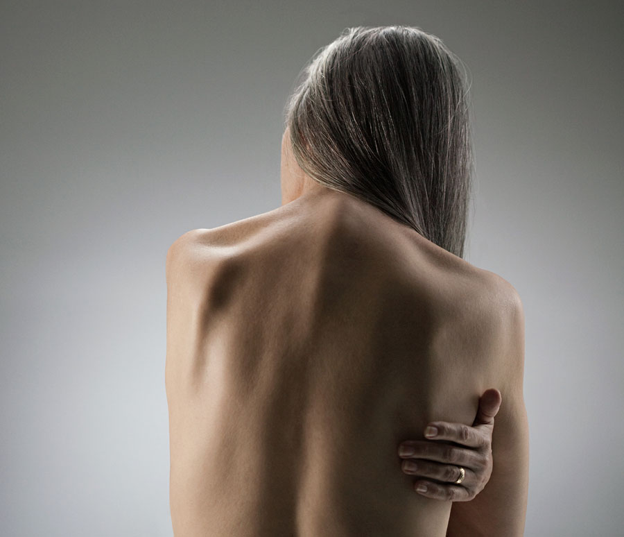 A slender woman with greying hair clutching at her back with her left hand.