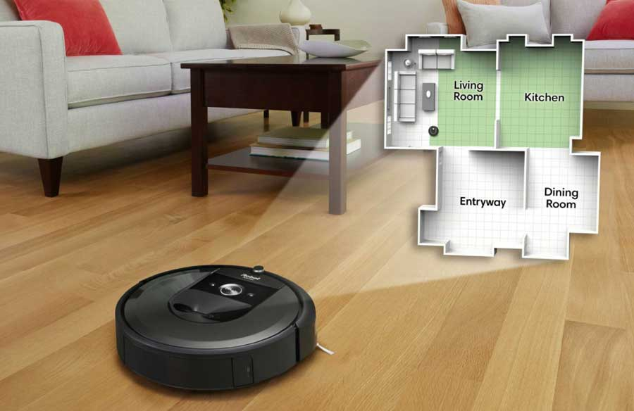 A Roomba vacuum on the hardwood floor of a family room.