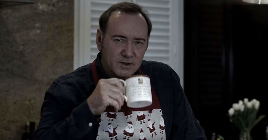Kevin Spacey wearing a snowman print holiday sweater and holding a coffee cup.