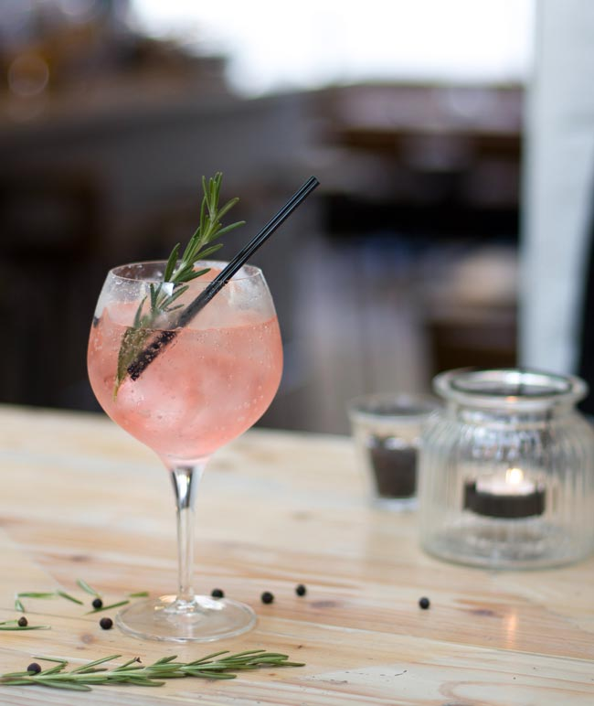 A festive pink cocktail with rosemary.