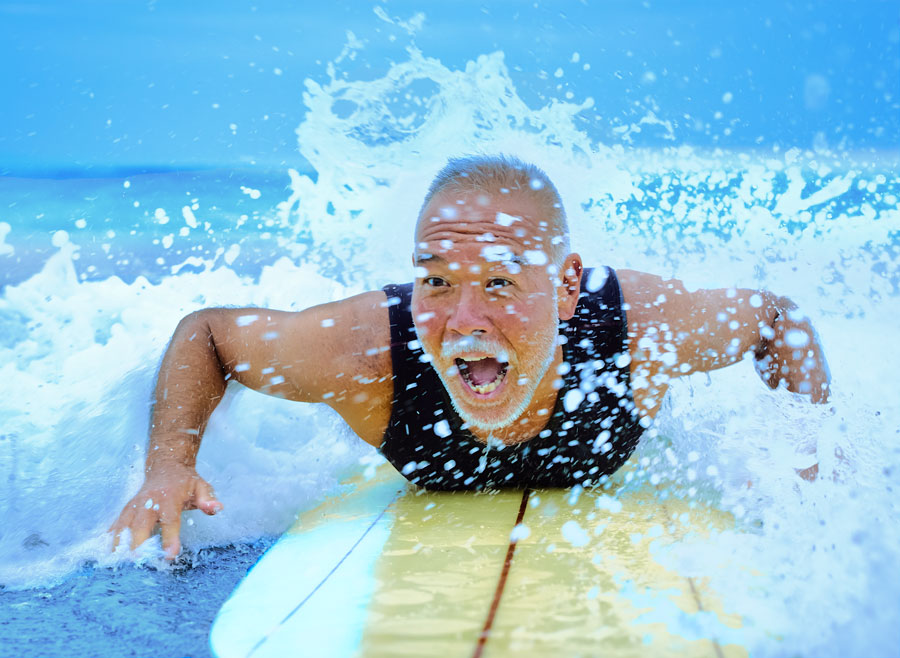 An older surfer excitedly catches a wave.