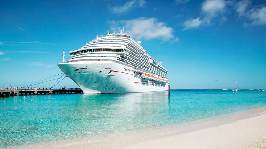 A cruise ship near the shore on a caribbean beach with white sand and bright blue water.