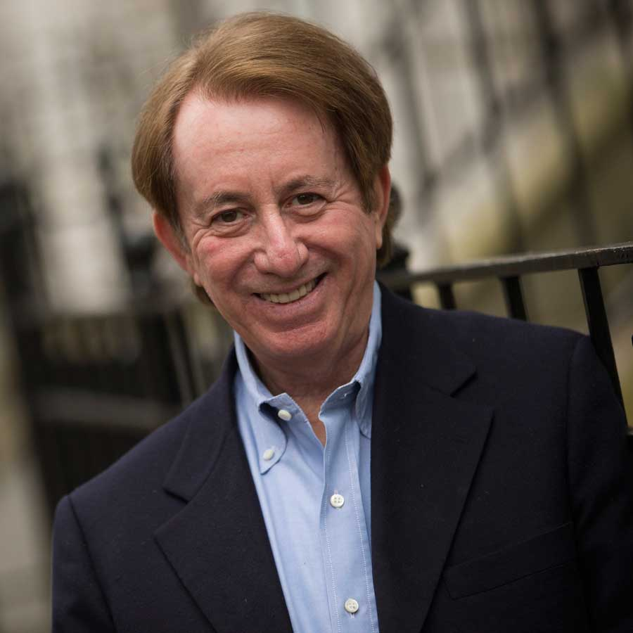 Mark Breslin smiling wearing a blue collared shirt and black suit jacket.