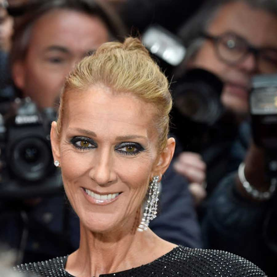 Celine Dion surrounded by photographers during paris fashion week, wearing a black sparkling dress and a dangling earring on her left ear.