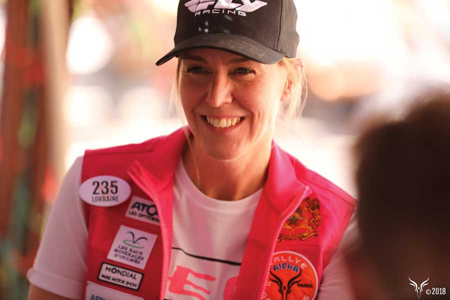 A woman smiling wearing a black hat and red racing vest.