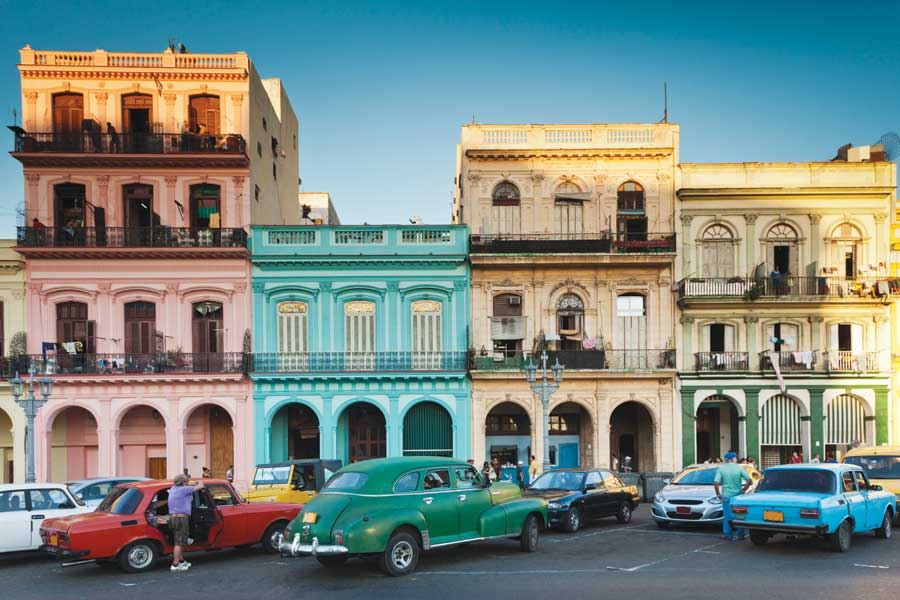 A block of colourful buildings, pink, bright blue and yellow in Old Havana.
