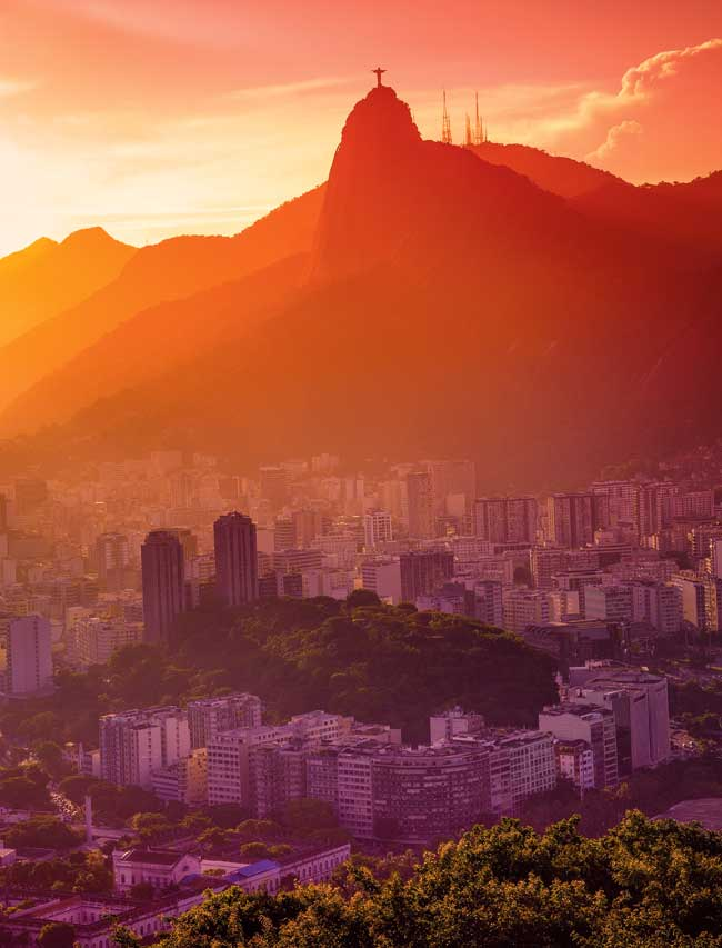 A photo of Rio at sunset with the remaining sun falling over the city and mountains in the background.