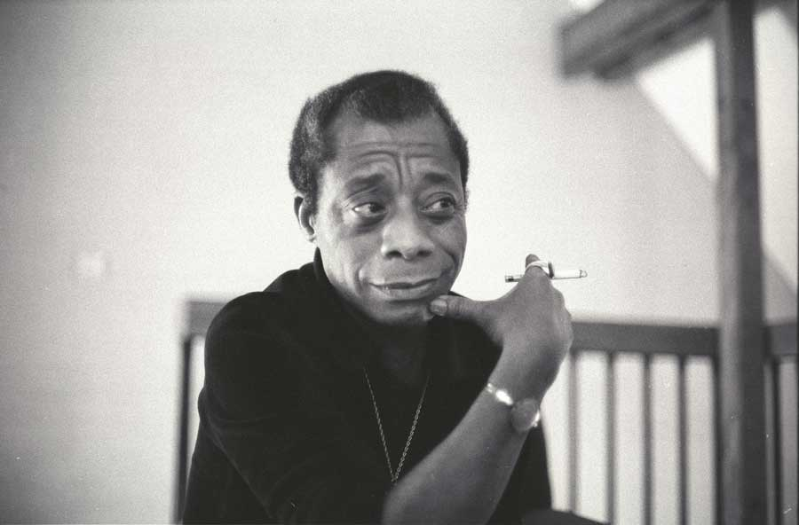 Civil rights activist and writer James Baldwin holding a cigarette, wearing a black shirt.