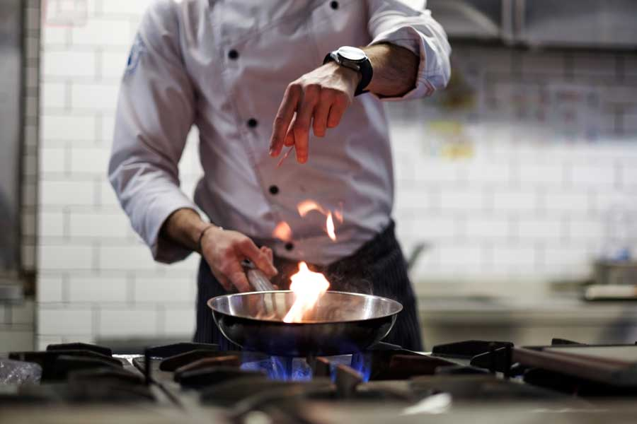 A chef sprinkling seasoning into a pan on the stove.