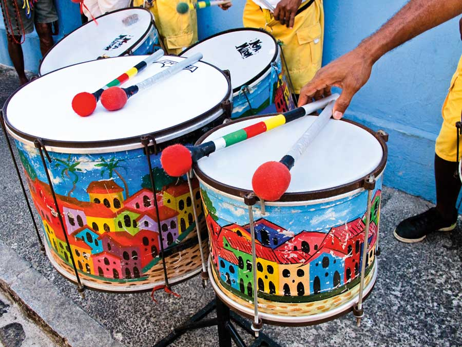 Drums with colourful houses painted on them in red, yellow, blue and green.