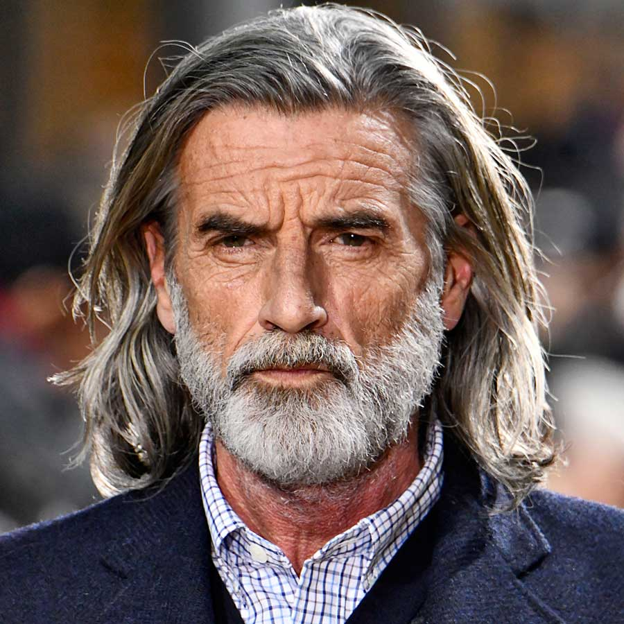 A closeup of a fashion model with long greying hair wearing a sport jacket.