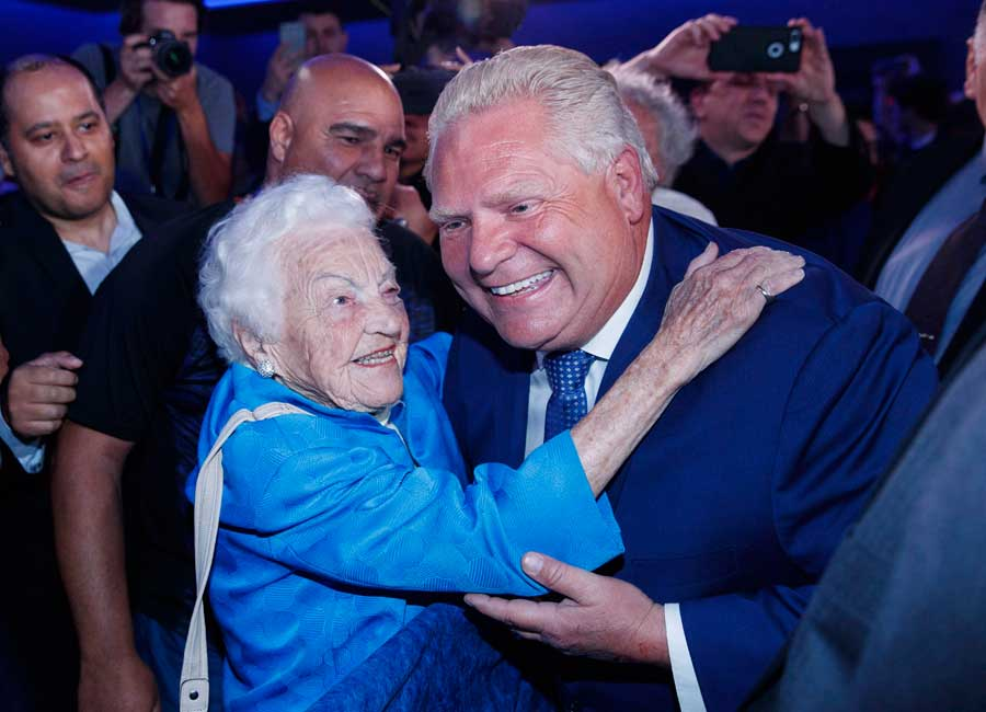 Ford and McCallion embrace at a political event both smiling.