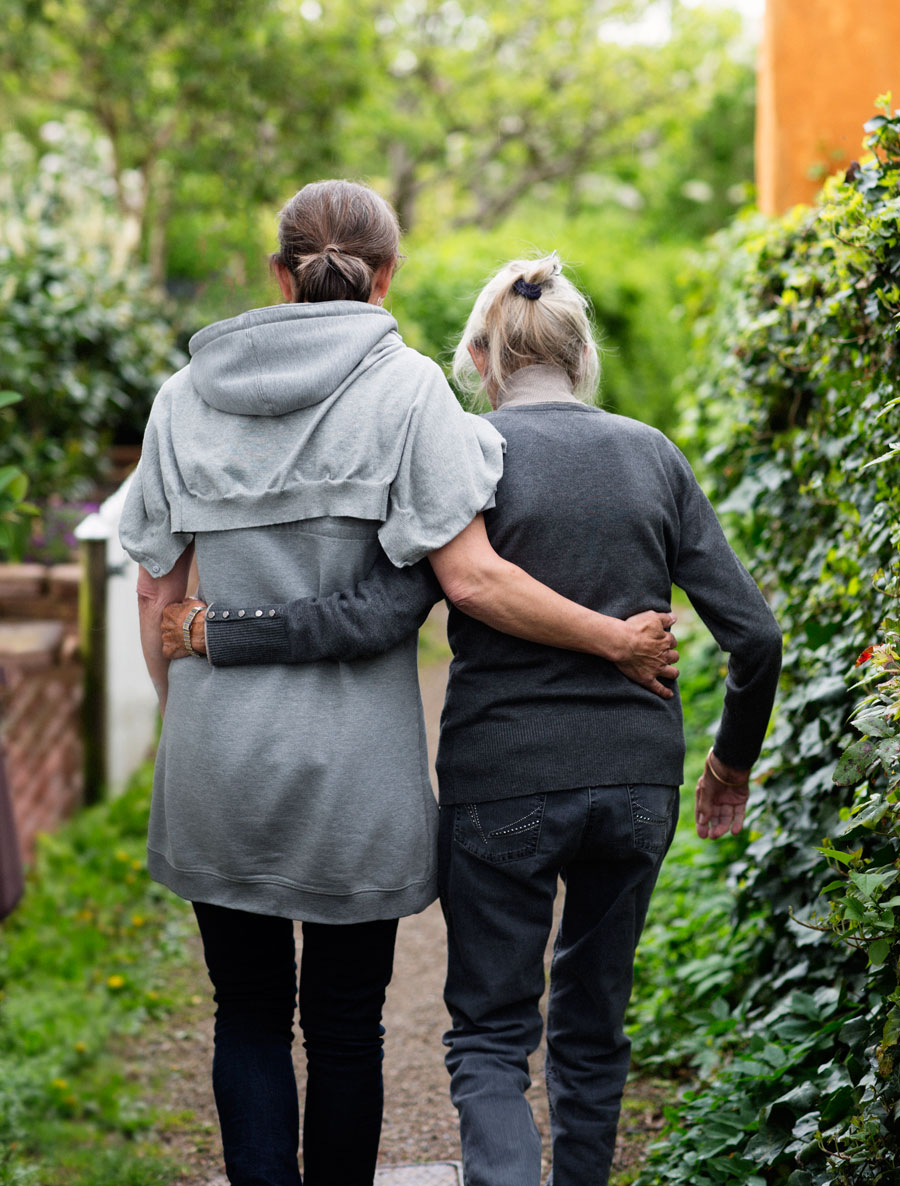 Two older women walk through the park arm in arm