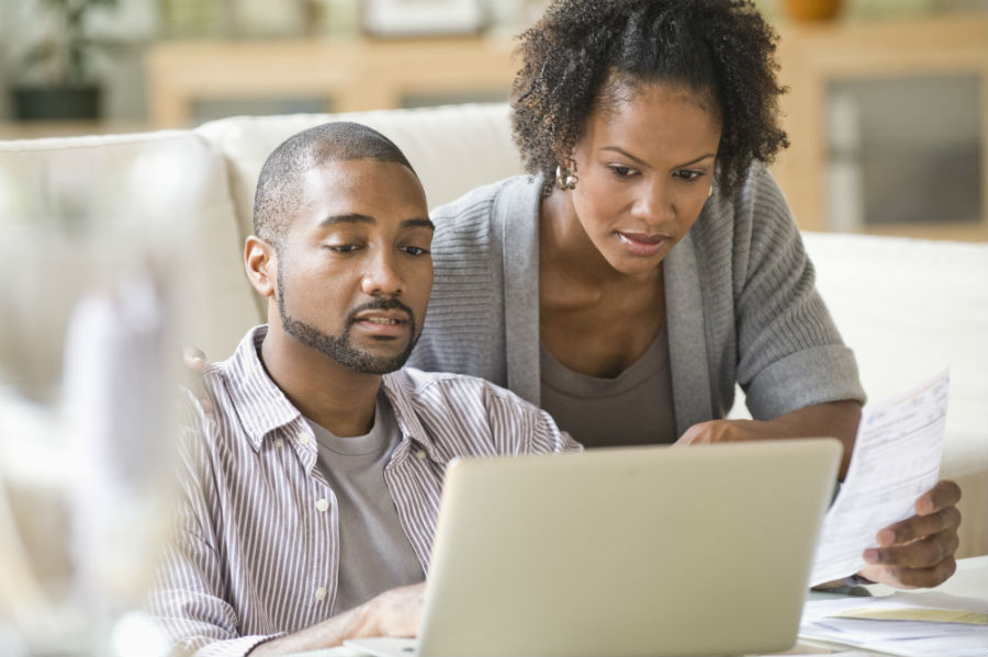 Couple looking laptop looking concerned.