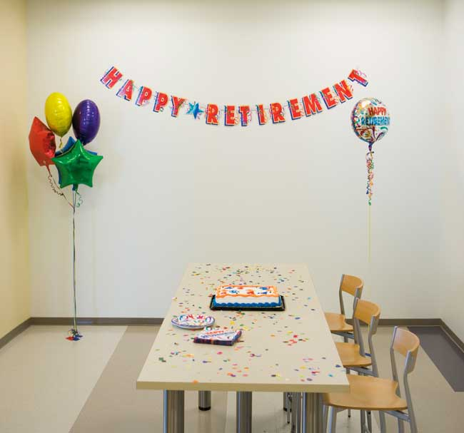 An office break room decorated with a happy retirement sign and balloons with a cake sitting on a table.