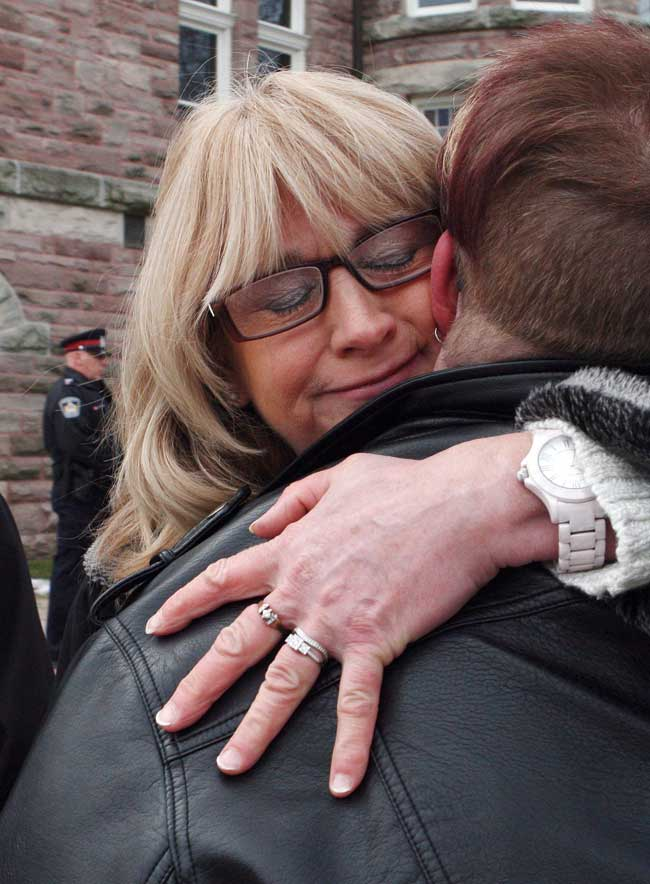 Andrea Silcox, daughter of victim Jane Silcox, is hugged by Laura Jackson, friend of victim Maurice Granat, outside the courthouse in Woodstock, Ont. on Jan. 13, 2017.