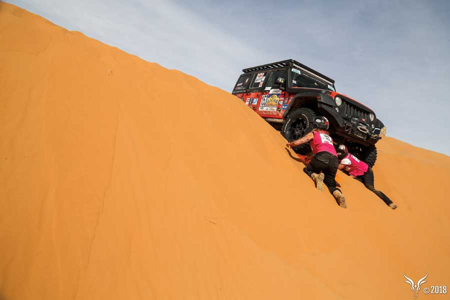 A jeep stuck on a sand dune in the Sahara Desert as two competitors attempt to dig it out.