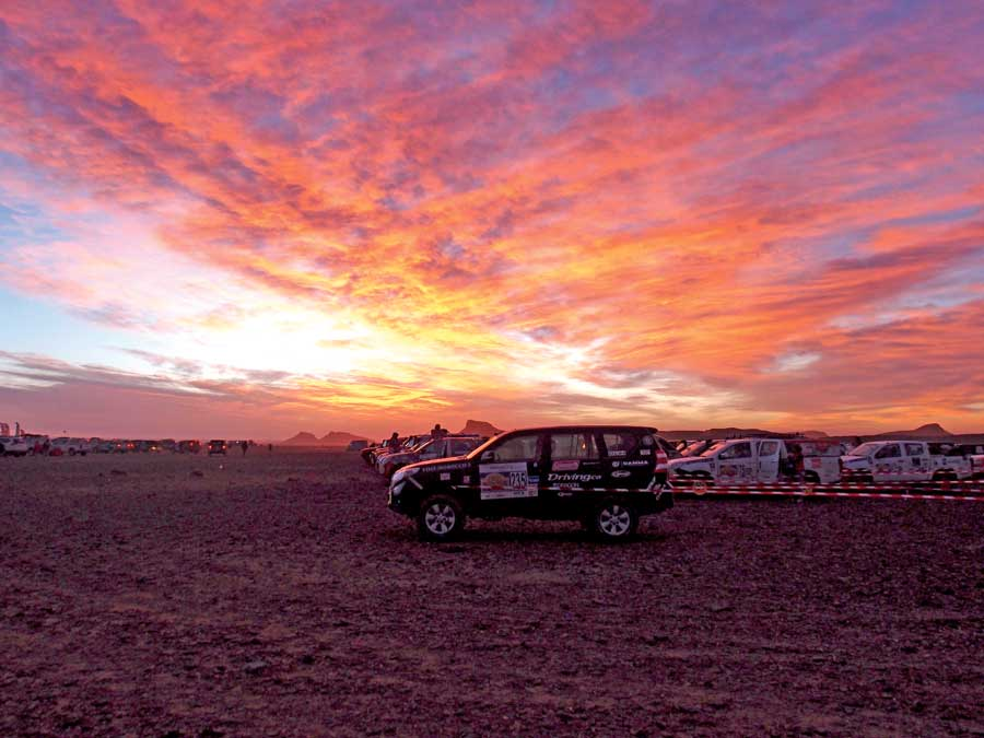 A truck sitting at the starting line with the a glowing sunset of pink, purple and orange in the background.