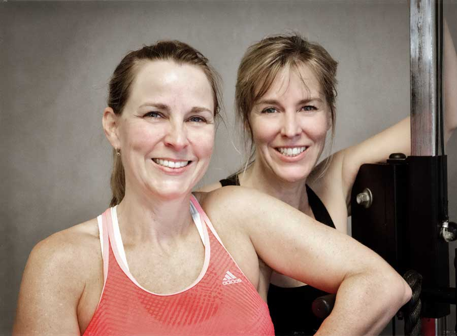 Two women posing together smiling while leaning against an exercise machine.