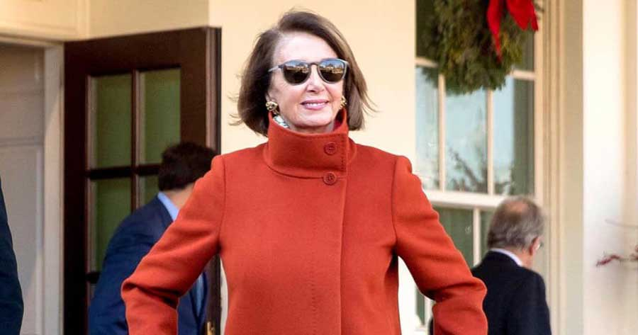 Nancy Pelosi walking out of the White House with her now famous red coat and sunglasses.