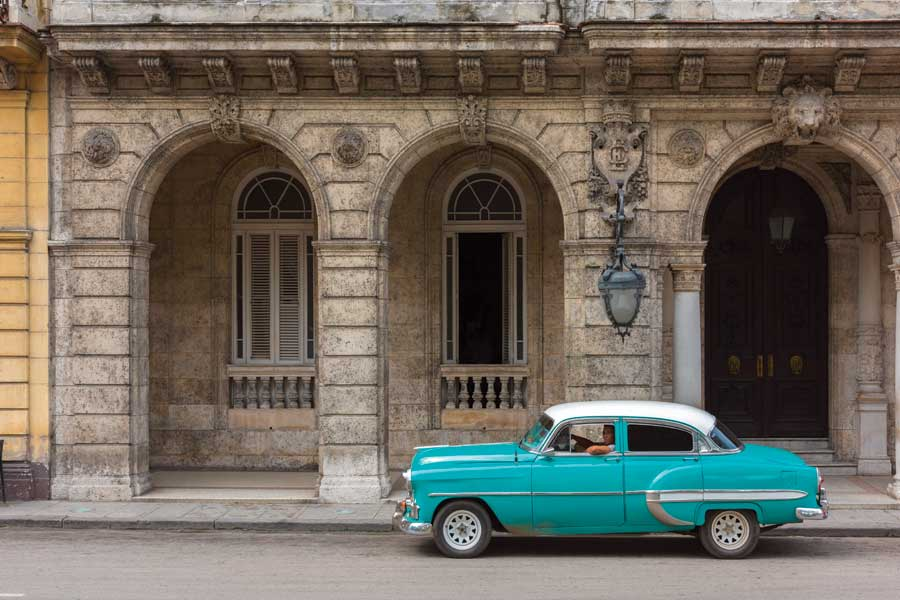A turquoise 1960s style car sitting in front of an old building in Old Havana.