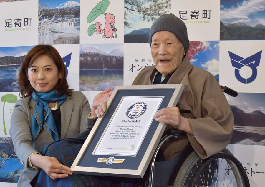 Masazo Nonaka of Japan (R), aged 112, receives a certificate for the Guinness World Records' oldest male person living title from Erika Ogawa (L), vice president of Guinness World Records Japan, in Ashoro, Hokkaido prefecture on April 10, 2018