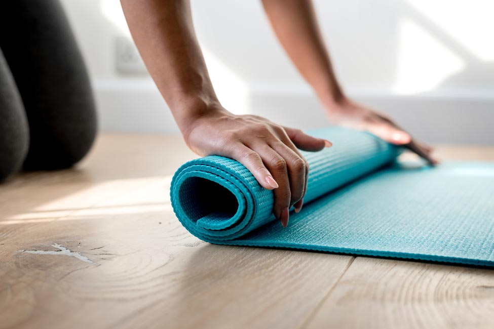 Woman unrolling blue yoga mat.