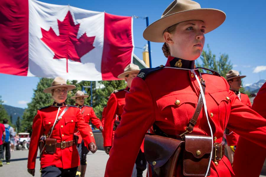 Female RCMP officer marches with other officers holding a large Canada flag behind her.