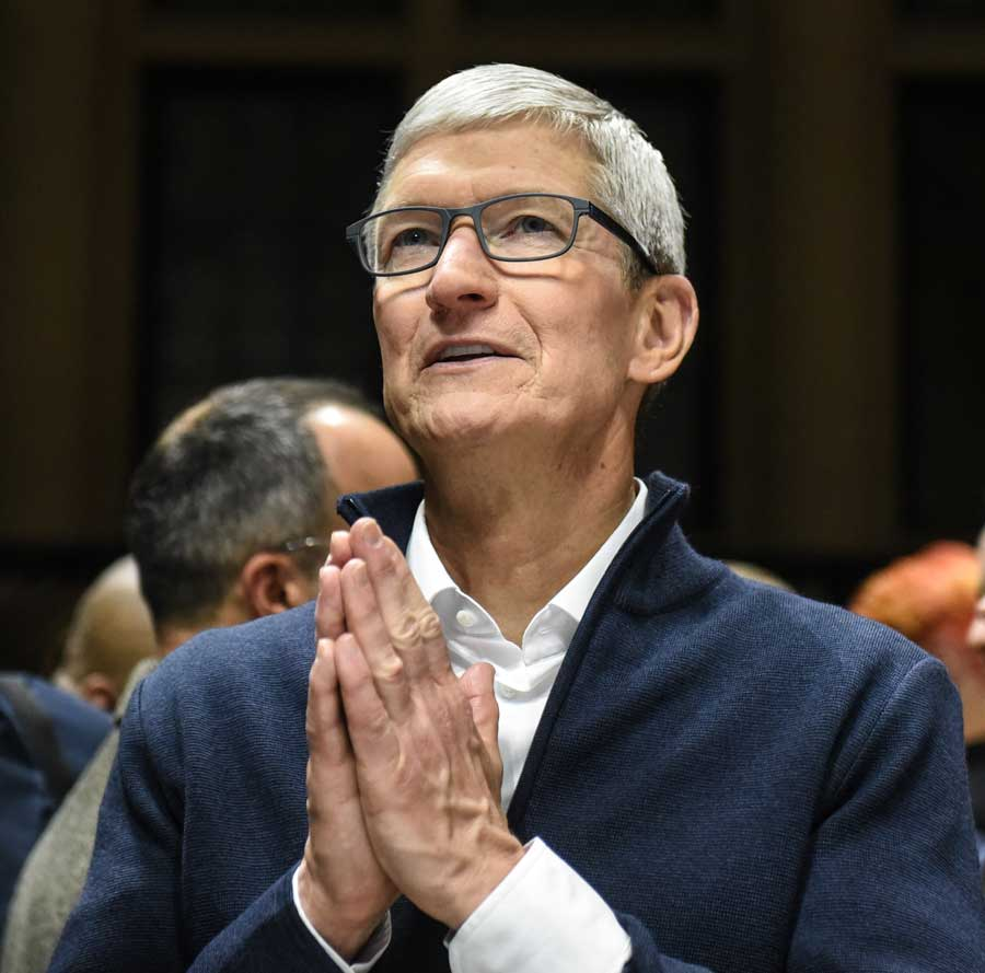 Apple CEO Tim Cook holding his hands together in prayer.