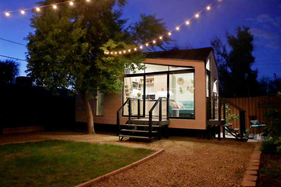 A tiny house with a large glass front window that the kitchen can be seen through.