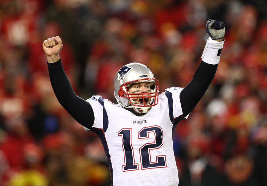 Tom Brady holds his hands up in victory.