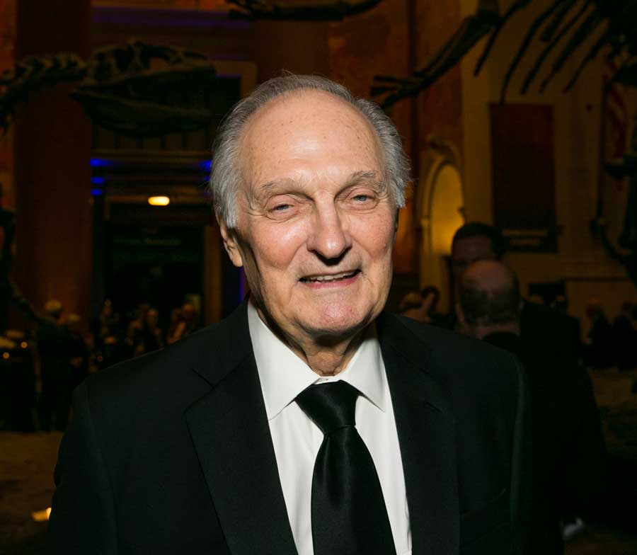 Alan Alda wearing a black suit with a white shirt and black tie smiling