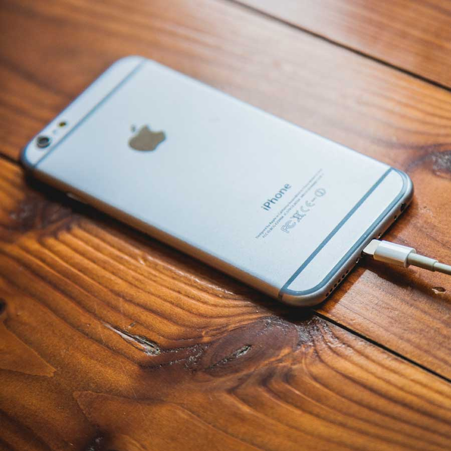 An iPhone laying face down on a wooden table.