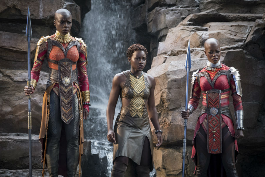 Three Wakanda warrior women stand in front of a waterfall, each wearing futuristic armour with a tribal element to it as well.